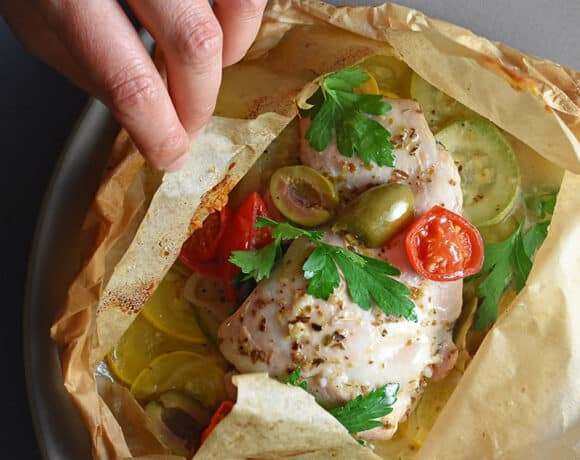 An overhead shot of an open lemon garlic chicken parchment packet filled with cooked chicken, olives, cherry tomatoes, and Italian parsley.