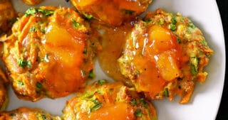 An overhead shot of Curry Turkey Bites topped with Apricot Ginger Sauce on a white plate.