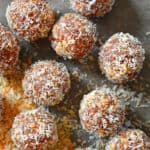 An overhead shot of healthy, paleo, no-cook energy balls on a piece of parchment paper.