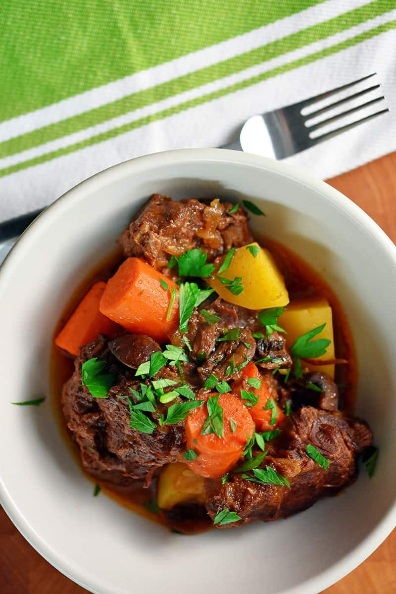 An overhead shot of a white bowl filled with paleo Instant Pot Beef stew with carrots and potatoes. There is a green and white napkin with a fork on top next to the bowl of stew.