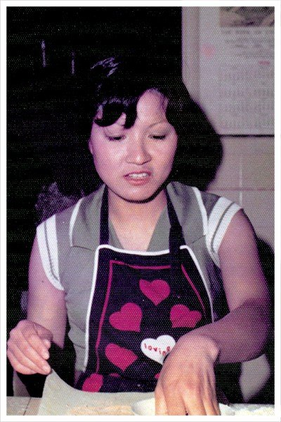 A grainy shot of a Chinese mom wearing a heart-covered apron.