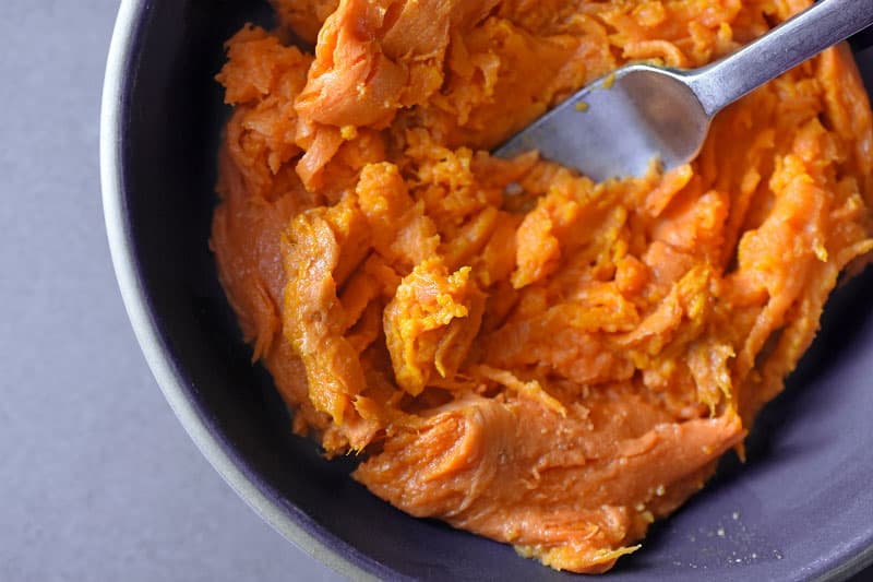 A bowl of cooked and mashed sweet potatoes with a fork in the bowl.