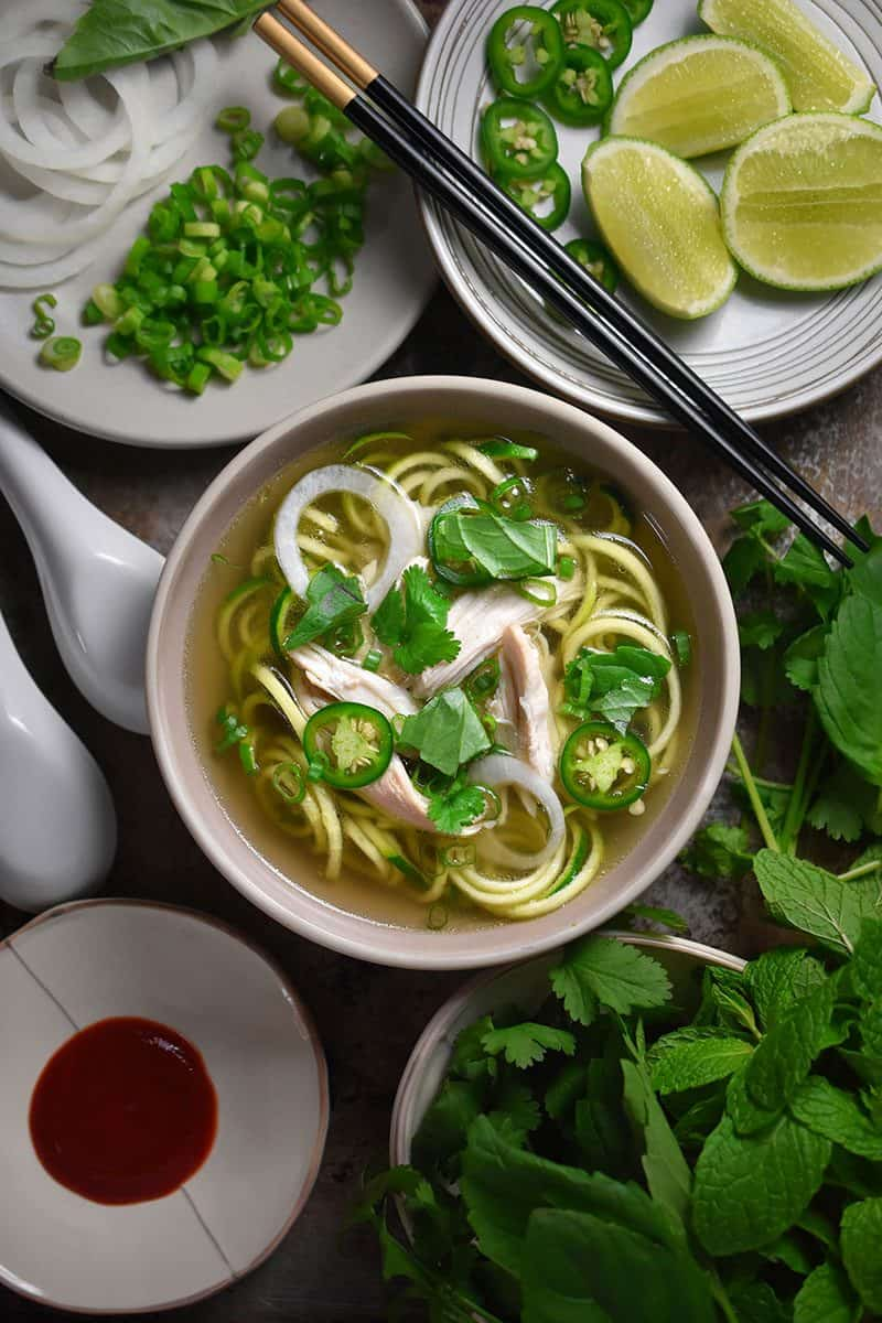 An overhead shot of a bowl of Instant Pot Chicken Pho on a dinner table