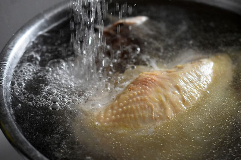 Running cold water on the cooked chicken to stop the cooking.