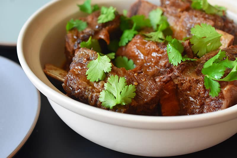 A closeup shot of a serving bowl filled with Instant Pot Korean Short Ribs