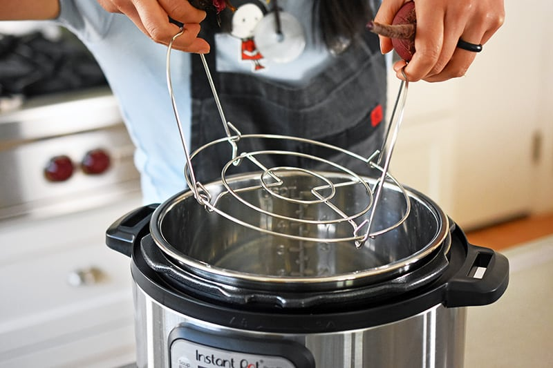 Someone inserting a metal rack into an instant pot.