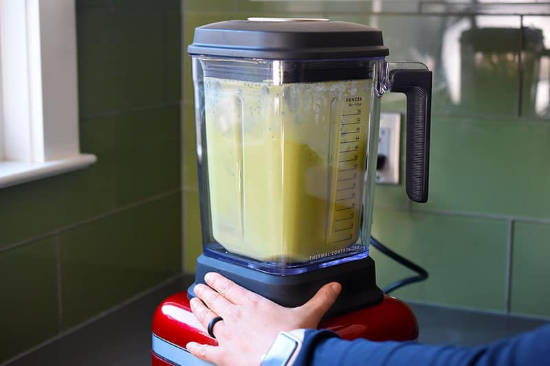 Someone blending the ingredients for the paleo matcha coconut gummies in a high speed blender.