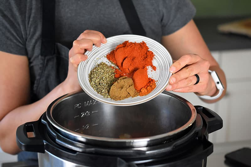 A closeup of a woman adding a plate filled with chili powder, oregano, cumin, and cayenne pepper into an open Instant Pot.