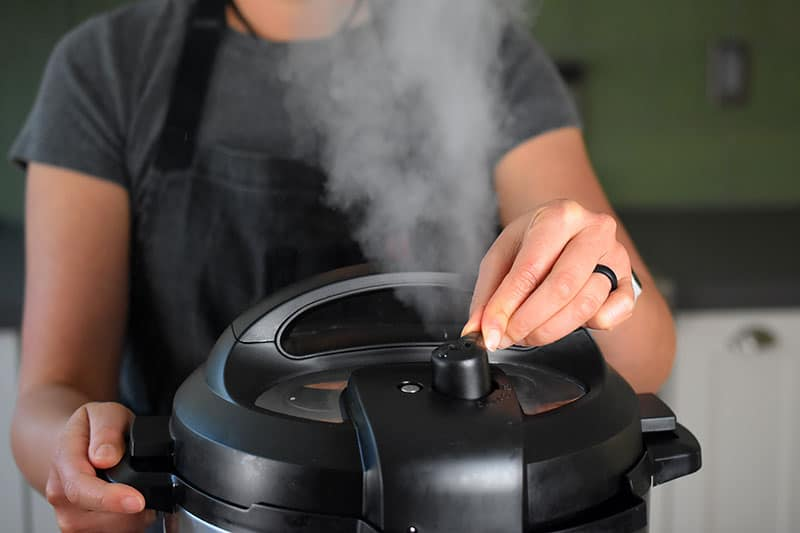 A closeup of a woman turning the pressure release valve on the lid of an Instant Pot. There is a stream of steam escaping from the valve.
