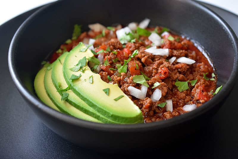 A side view of a black bowl on top of a black plate. The bowl is filled with Instant Pot Ground Beef Chili and topped with sliced avocado, diced white onions, and minced cilantro leaves.