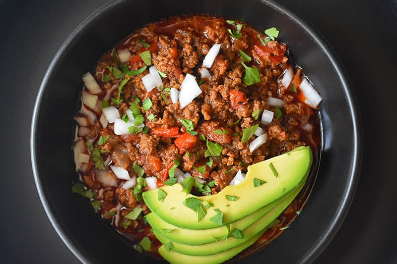 An overhead shot of a bowl of Instant Pot Ground Beef Chili topped with sliced avocado and diced white onions