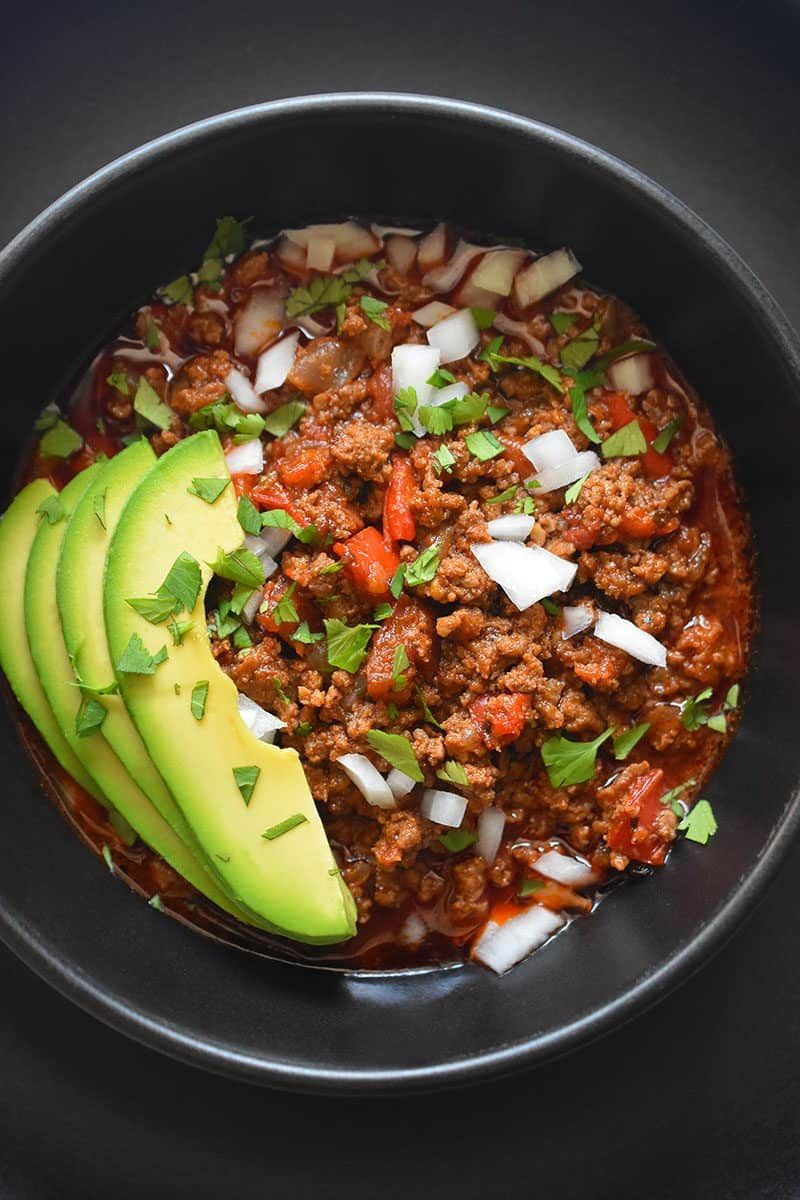 A top view of a black bowl on top of a black plate. The bowl is filled with Instant Pot Ground Beef Chili and topped with sliced avocado, diced white onions, and minced cilantro leaves.
