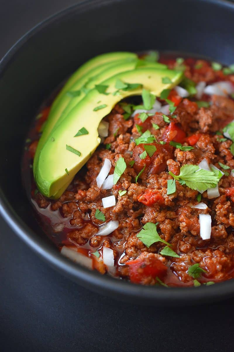 A close up image of Instant Pot Ground Beef Chili topped with sliced avocado, diced onions, and chopped cilantro in a black bowl.
