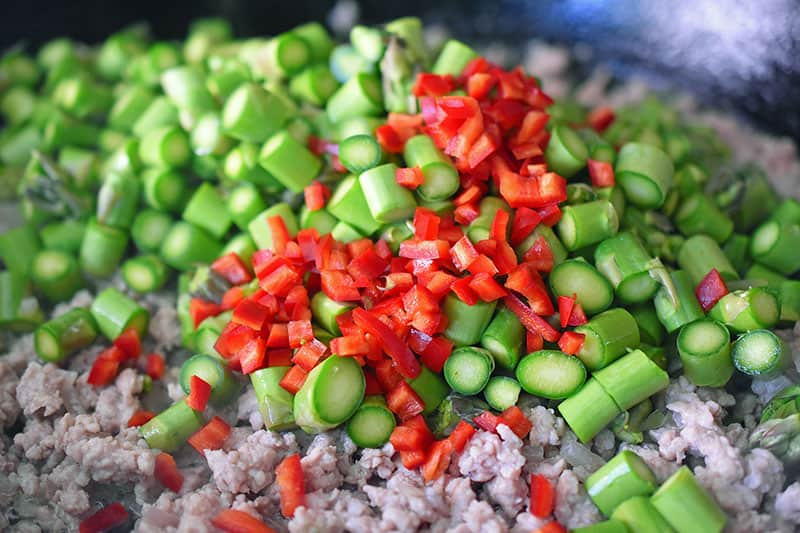 Adding minced chilis to the asparagus and ground pork in the skillet