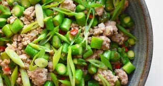 An overhead closeup shot of Spicy Pork and Asparagus Stir-Fry in a serving bowl.