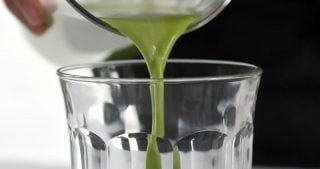 Someone pouring Cold Matcha Latte into a clear glass.