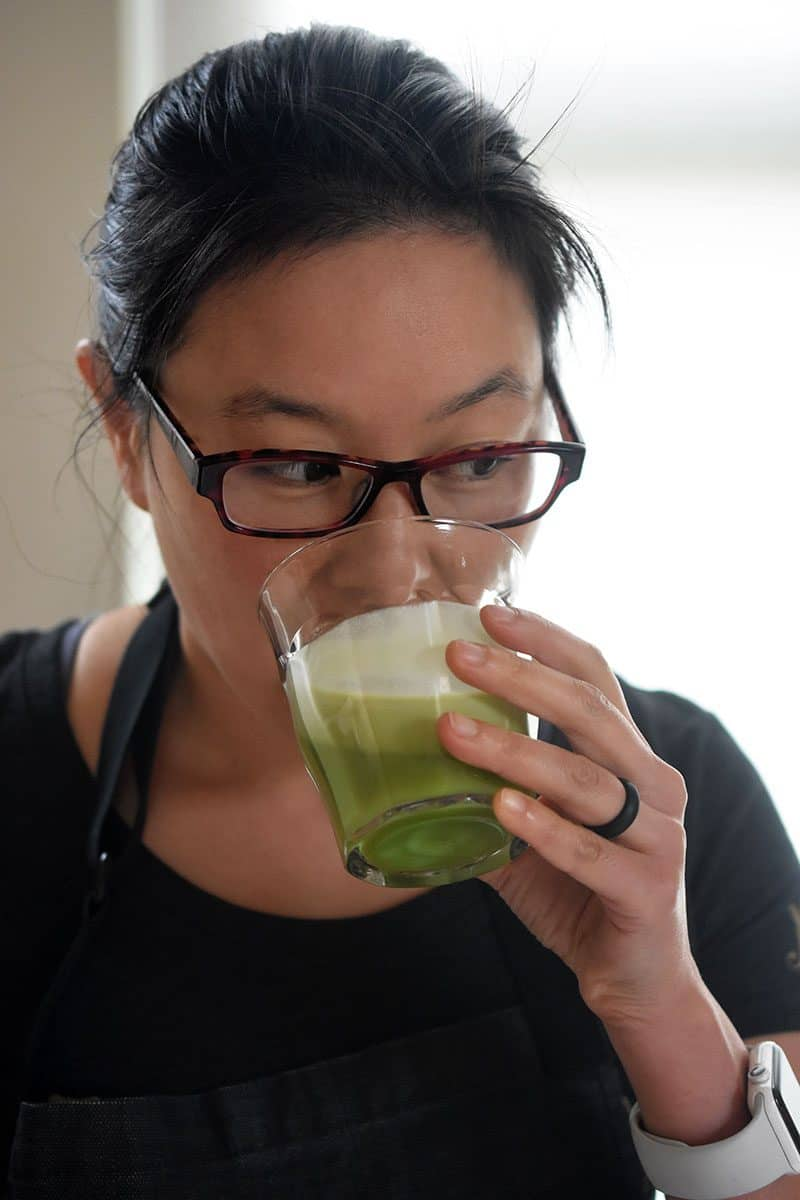 A brunette woman in glasses is drinking a cup filled with Cold Matcha Latte