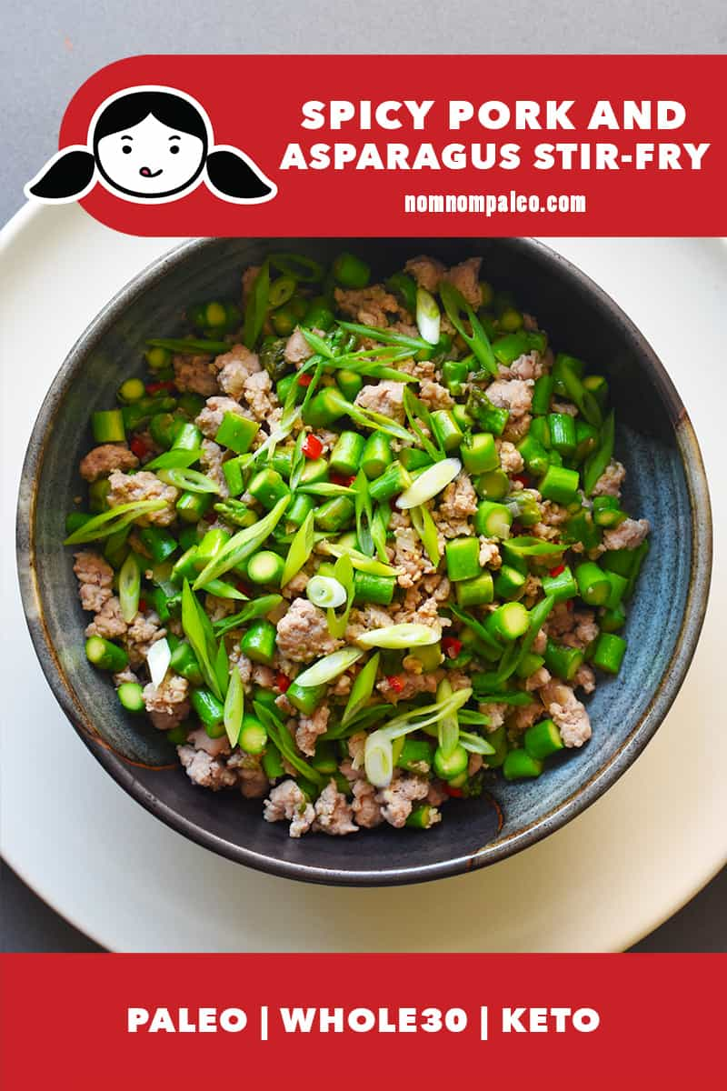 An overhead shot of a bowl of Spicy Pork and Asparagus Stir-Fry. There is a red banner with the Nom Nom Paleo logo that also states that the dish is paleo, Whole30, and Keto.