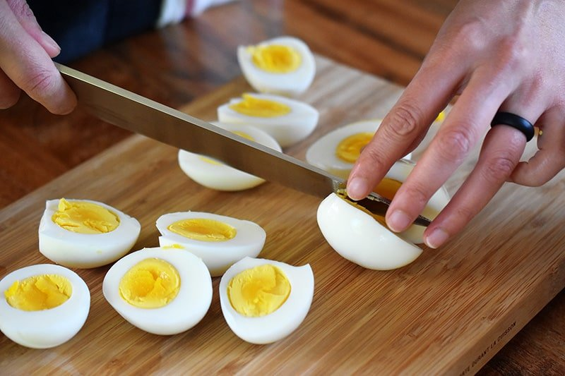 Someone slicing a bunch of hard cooked eggs on a wooden cutting board.
