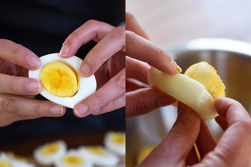 Someone popping the egg yolks out of halved hard cooked eggs.