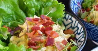 An overhead shot of Bacon Deviled Egg Salad in blue and white bowls.