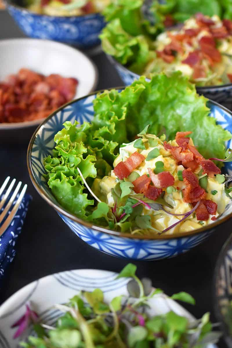 A closeup of Bacon Deviled Egg Salad on a lettuce leaf in a blue and white bowl.