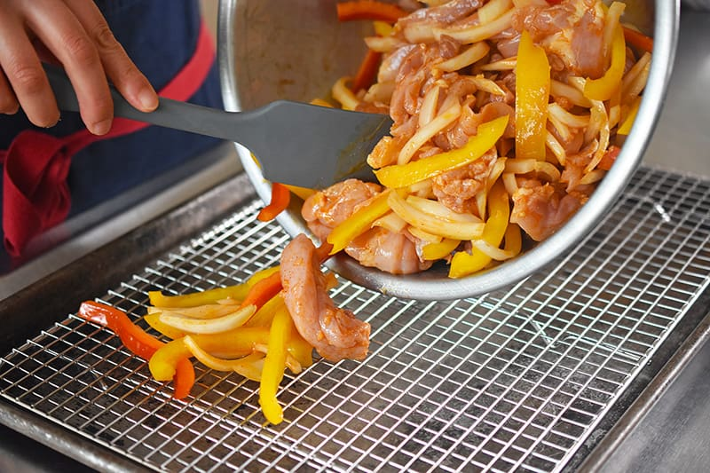 Placing the chicken fajitas and vegetables on a wire rack on top of a rimmed baking sheet