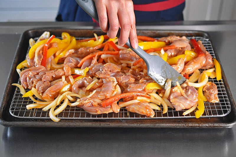 Using a silicone spatula to make the Sheet Pan Chicken Fajitas in a single layer on the wire rack