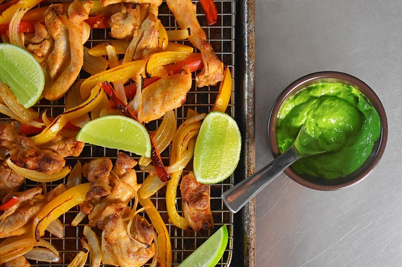 Overhead shot of Sheet Pan Chicken Fajitas and a bowl filled with Avocado Crema