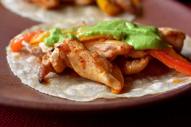 A closeup of a grain-free tortilla topped with Sheet Pan Chicken Fajitas and Avocado Crema