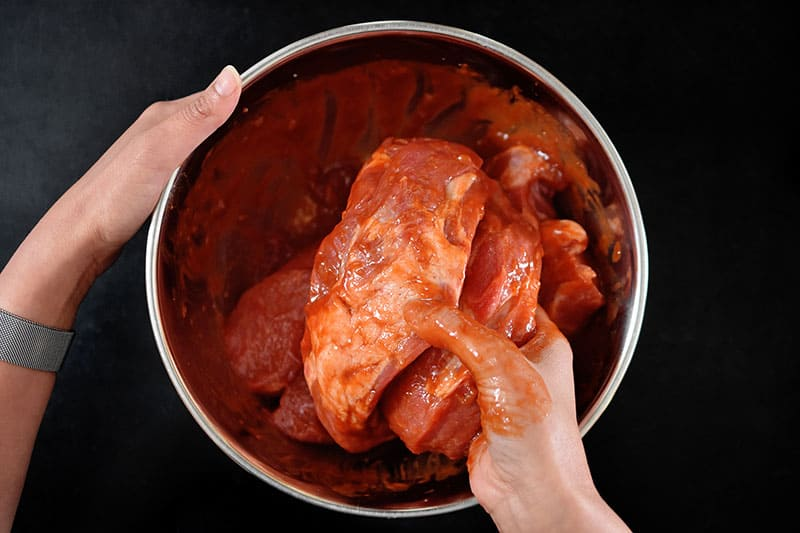 A hand is pictured mixing the Paleo Char Siu marinade with the pork shoulder pieces.