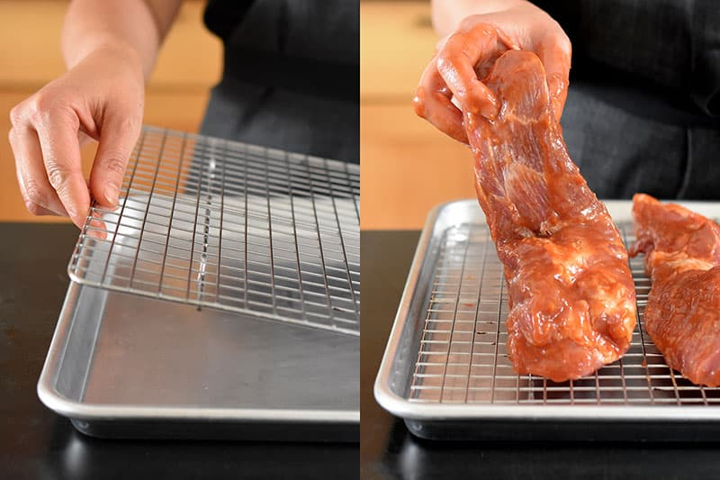 The marinated pork shoulder pieces are placed on a wire rack in a rimmed baking sheet.