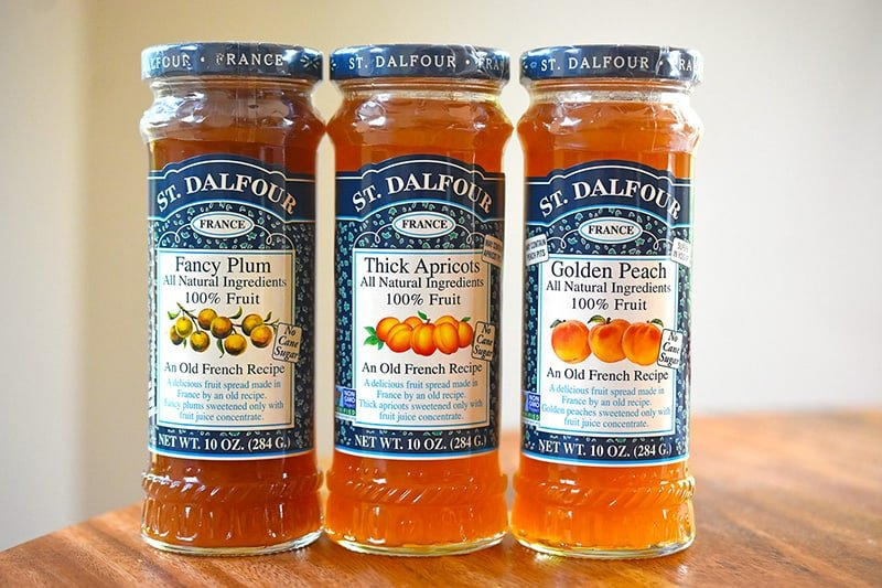Three jars of St. Dalfour Whole30-friendly jam. There is a plum, apricot, and peach jam bottles.