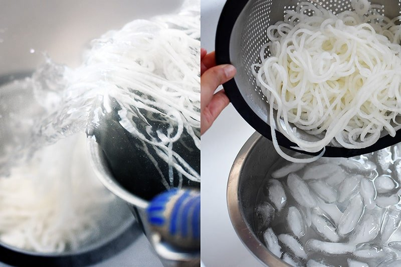 Someone draining the daikon noodles from the pot and placing them in an ice water bath.