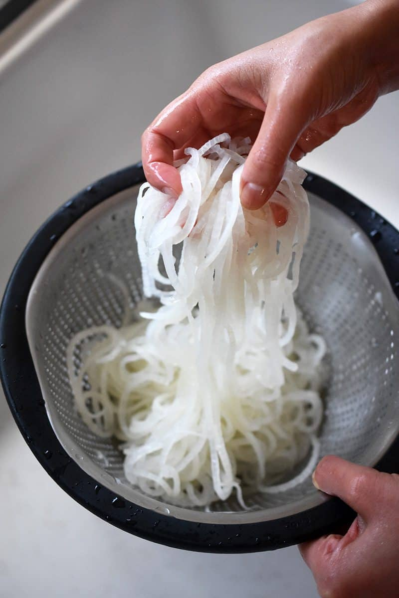 Someone pulling the chilled daikon noodles up from the colander.