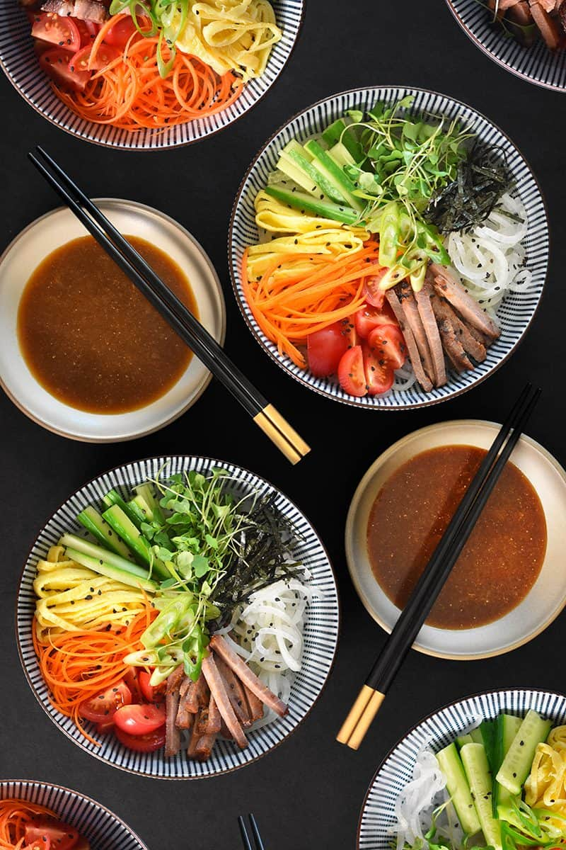 Several bowls of paleo cold ramen surrounded by bowls of paleo and soy-free dipping sauce.