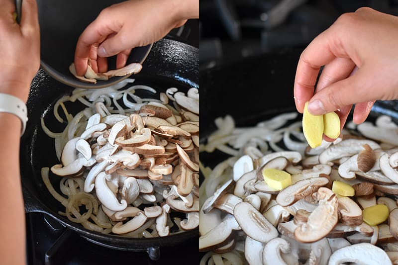 Adding thinly sliced shiitake mushrooms and ginger slices to a cast iron skillet filled with cooked onions.