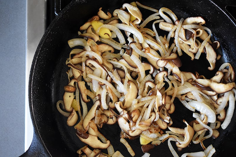 An overhead shot of onions, shiitake mushrooms, and ginger sautéing in a cast iron skillet.
