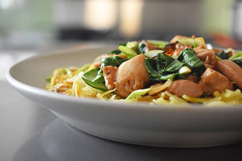 A side view of a white shallow bowl filled with Whole30, gluten-free, grain-free, and Paleo Chicken Chow Mein