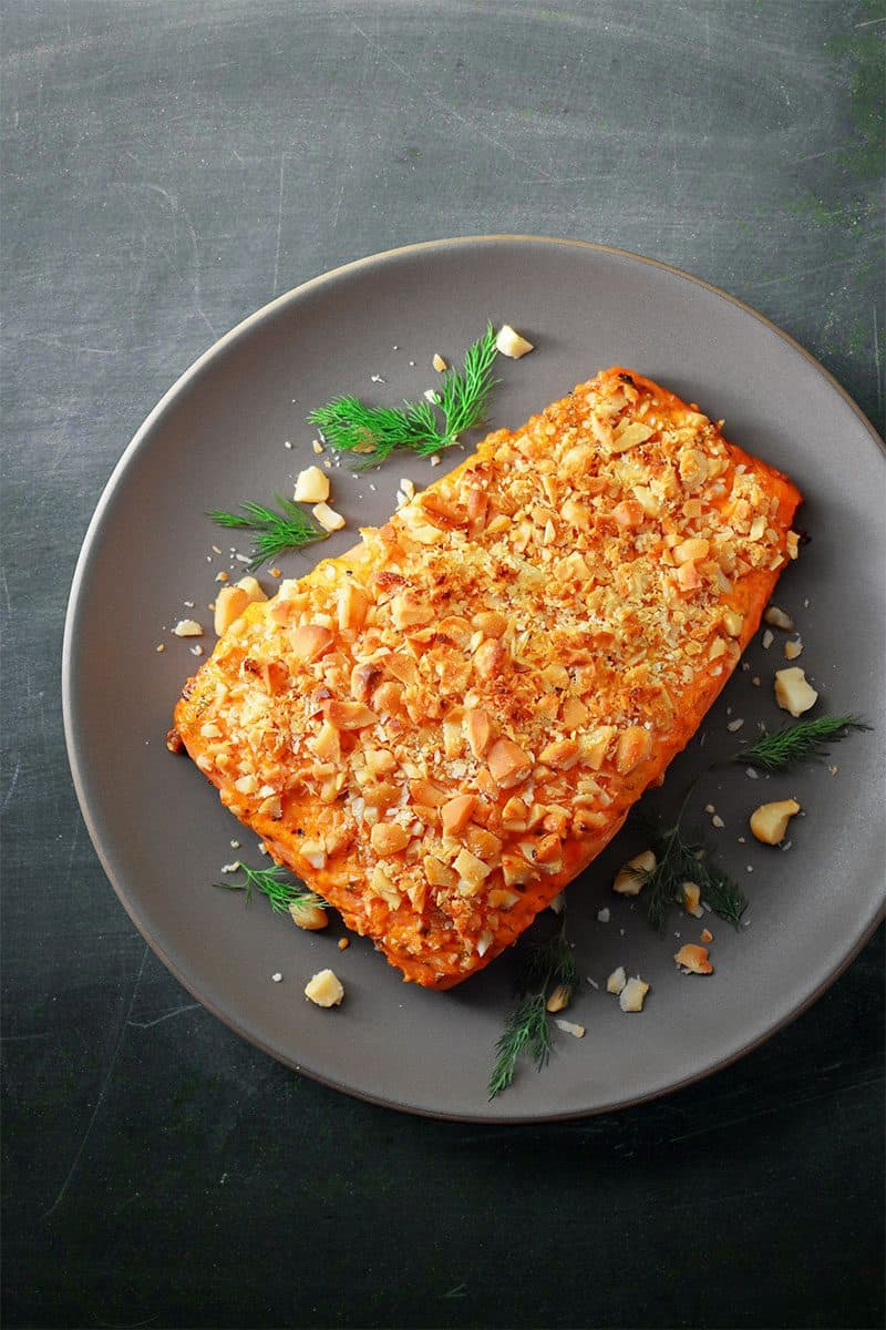 A plate with paleo Macadamia-Crusted Sriracha Ranch Salmon.