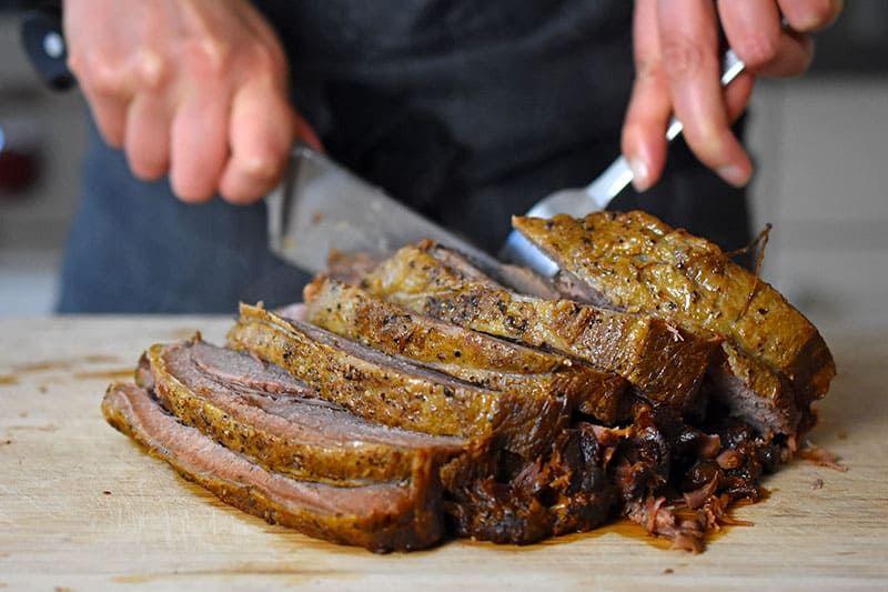 Instant Pot Yankee Pot Roast is sliced on a wooden cutting board