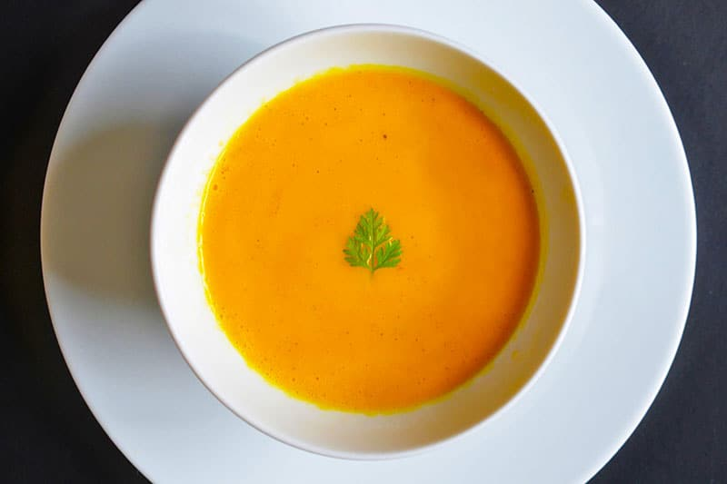 An overhead shot of a bowl of paleo and Whole30 carrot and cardamom soup in a white bowl.