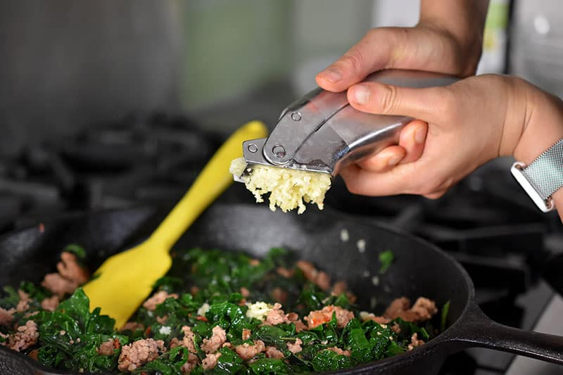 Minced garlic is added from a garlic press to the cooked sausage and kale in the cast iron skillet.