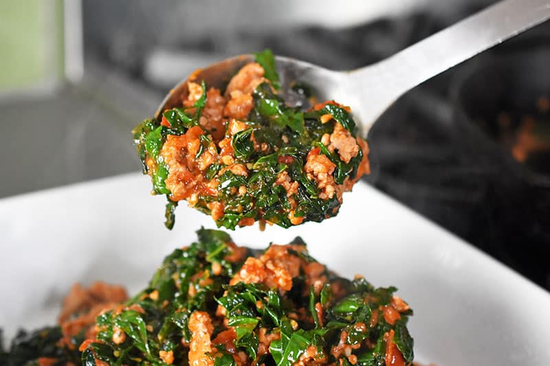A large spoon transfers the cooked sausage, kale, and marinara to the greased casserole dish.