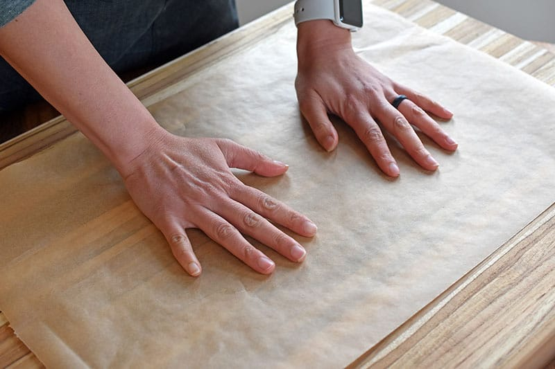 A piece of parchment paper is placed on a large wooden cutting board.