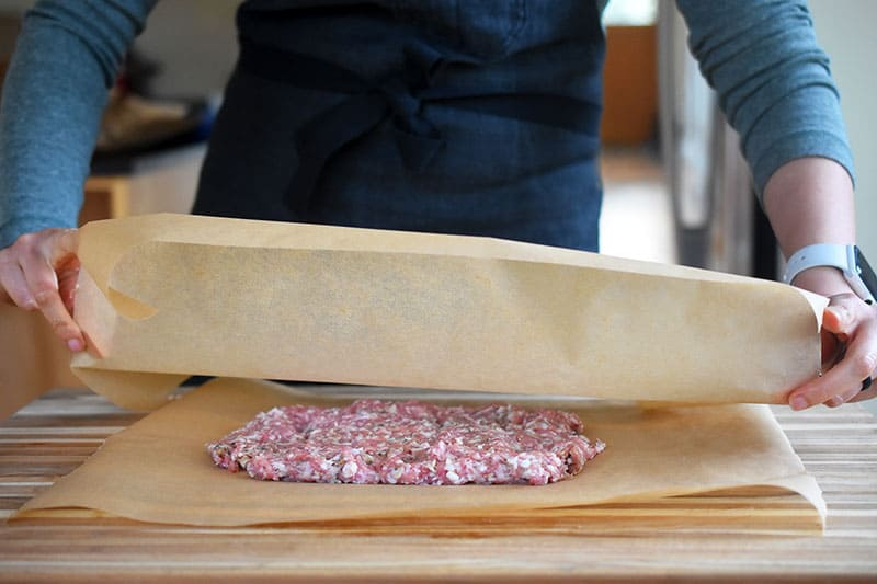 A rectangular block of sausage is placed between to pieces of parchment paper.