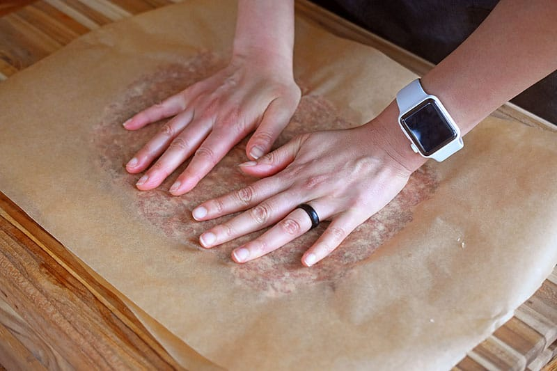 A meatza crust in between two pieces of parchment paper is pressed flat with two hands.
