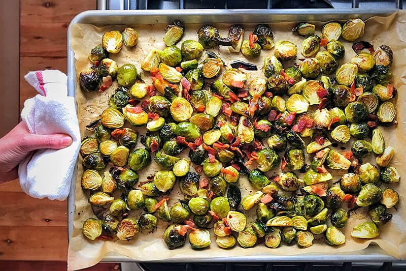An overhead shot of a tray of roasted Brussels sprouts and bacon fresh out of the oven.