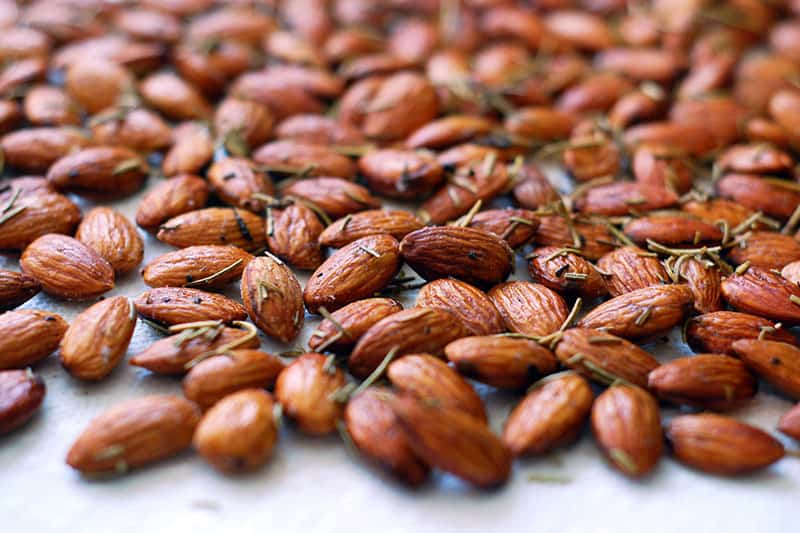 A closeup shot of roasted rosemary almonds, a simple party appetizer.