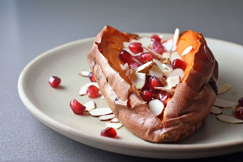 A side shot of a baked sweet potato split open and topped with toasted almonds, pomegranates, and balsamic vinegar.
